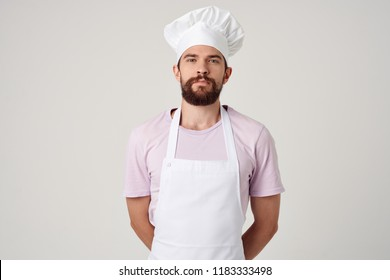 cook in an apron and in a pink T-shirt on a gray background