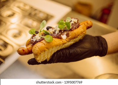 cook in black gloves holds hot dog. The cook prepares a hot dog, adding the sauce to the sausage. hamburgers, hot dog. concept of fast food. cook hot-dog. vintage photo processing