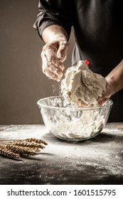 A cook in black knead the dough in a glass bowll bowl for cooking bread in the kitchen. Yeast dough made with love. Dough in her hands.