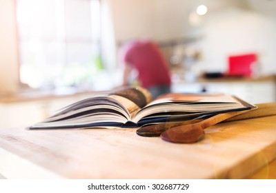 Cook book laid on a kitchen table with two wooden spoons