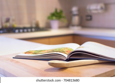 Cook book put on a kitchen table with a wooden spoon in the foreground. Kitchen is visible in the background.