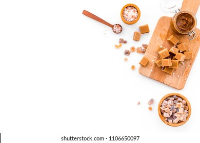 Cook caramel sauce. Melted caramel in glass jar, caramel cubes on cutting board, sugar and salt on white background top view space for text