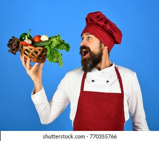 Cook with cheerful face in burgundy uniform holds vegetables in wicker bowl. Chef holds lettuce, tomato, pepper and mushrooms. Vegetarian diet concept. Man with beard on blue background.