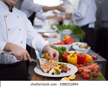 cook chef decorating garnishing prepared meal dish on the plate in restaurant commercial kitchen