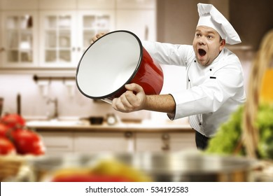 Cook chef in kitchen and blurred vegetables