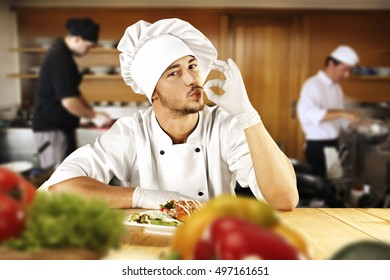 cook chef in kitchen and fresh vegetables on table