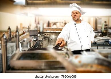 Cook chef in kitchen interior. Blurred kitchen tools. Crazy guy.