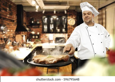 cook chef in kitchen and steak