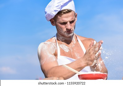 Cook or chef with sexy muscular shoulders and chest covered with flour. Baker concept. Man on busy face wears cooking hat and apron, sky on background. Chef cook preparing dough for baking with flour.