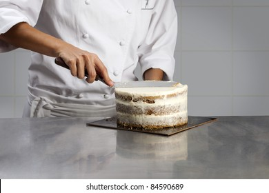 Cook coating a cake with cream