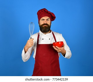 Cook with confused face in burgundy hat and apron uses bowl and whisk. Chef with red plate and whipping utensil. Kitchen tools concept. Man or hipster with beard holds kitchenware on blue background