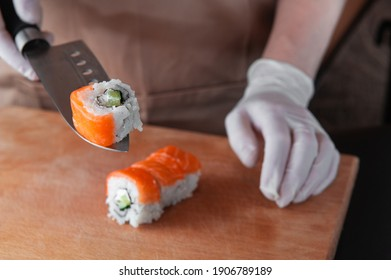 Cook cuts sushi and holds a piece on the blade of a knife