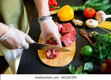 Cook cutting meat on a board and fresh raw vegetables on a dark table. Top view. Food concept