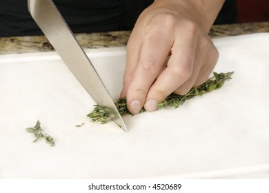 Cook cutting thyme in preparation for a meal.