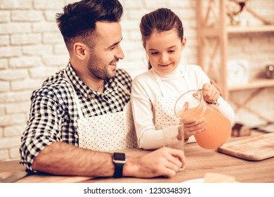 Cook Food at Home. Father and Daughter. Pour Juice in Glass. Happy Family. Father's Day. Girl and Man Cook Food. Man and Child at Table. Spend Time Together. Girl with Carafe in Hand. Girl with Carafe