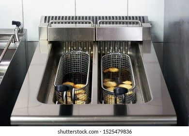 The cook fries french fries in a deep fryer. Preparation in a deep fryer. Deep fryer with boiling oil on restaurant kitchen