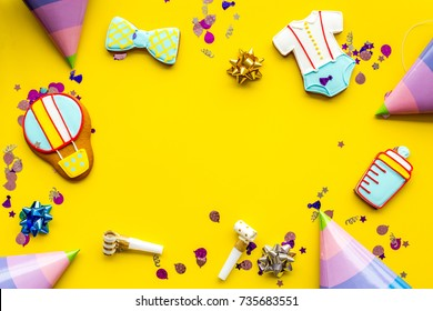 Cook gingerbread cookies with ticker tape for baby shower on yellow colorful background top view mockup