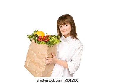 cook girl holding a paper bag with vegetables - isolated on white
