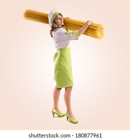 cook girl with large delicious spaghetti on a beige background