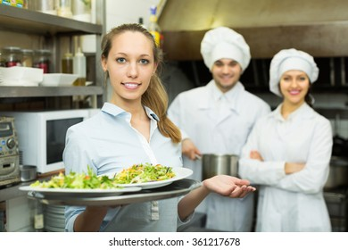 Cook gives to female waitress plates with prepared meal at restaurant kitchen