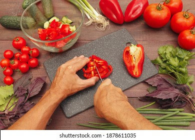 Cook hands cut fresh bellpepper for salad on a rustic wooden table.