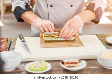 Cook hands making japanese sushi roll. Japanese chef at work preparing delicious sushi roll with eel and avocado. Appetizing japanese food.