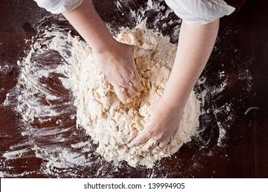 Cook hands preparing pizza dough on a wooden table overhead shot