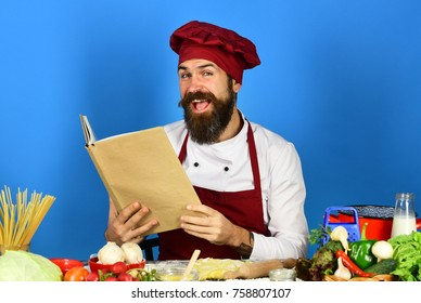 Cook with happy face in burgundy uniform reads cook book. Homemade food concept. Chef near pasta, vegetables and dough on table. Man with beard holds recipe book or menu on blue background