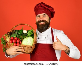 Cook with happy face in burgundy uniform holds vegetables in wicker basket showing thumbs up. Healthy cooking concept. Man with beard on red background. Chef hold cabbage, radish, broccoli and lettuce