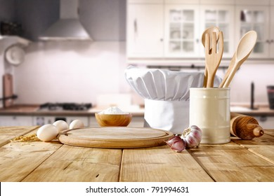 Cook hat on wooden table. Kitchen interior. Few kitchen tools. Free space for your decoration.