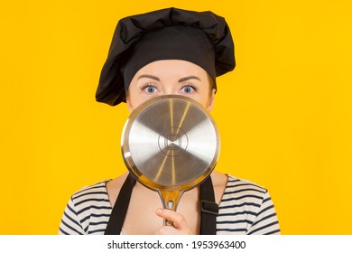Cook hides his face behind a saucepan. Portrait of a female chef with a saucepan in front of her face. Cook tries to hide. Girl chef on a yellow background. Cook in a black chef's hat.