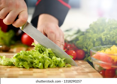 Cook holds knife in hand and cuts on cutting board green salad or fresh vegetable soup with vitamins. Raw food and vegetarian recipe book in modern society popular concept.