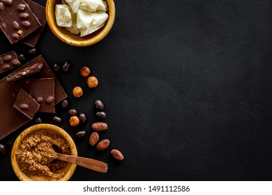 Cook homemade chocolate with bars, nuts, coffee beans on black background top view mock up
