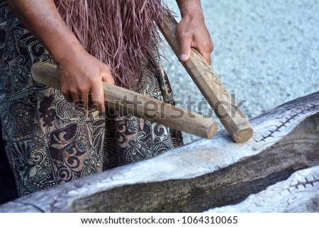 Cook Islander man plays on a large wooden log Pate drum instrument in Rarotonga, Cook Islands.Rael people. Copy space