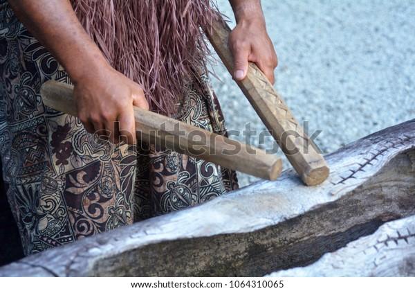 Cook Islander man plays on a large wooden log Pate drum instrument in Rarotonga, Cook Islands.Rael people. Copy space