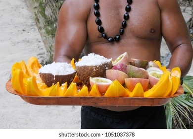 Cook Islander man serves coconut and papaya fruit on a tray in Rarotonga, Cook Islands. Food background and texture. Real people. Copy space