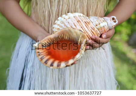 Cook islander woman holds a Conch Shell Horn.Seashell horn trumpet sound carries over a long distances and used by South Pacific people as signaling devices rather than played musical instrument.