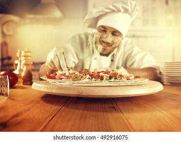 cook in kitchen with big wooden table of food