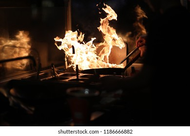 The cook in the kitchen holds a frying pan wok with an open flame and tries to extinguish it with water