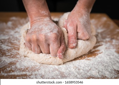 the cook kneads the dough with his hands on a wooden Board close-up. suitable for pizza, pies, cakes, cupcakes