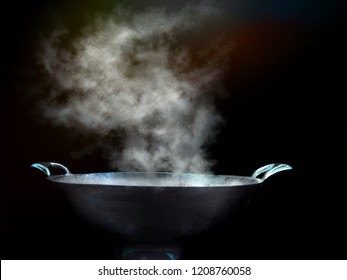 Cook with a large steel pan, boiling, steaming, old-fashioned with smoke and floating steam, and evaporated into the air.