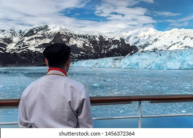 Cook is looking on the Hubbard Glacier. He is from India and his job is to work on a cruise ship. Crew member enjoying an amazing view. Chef is wearing red scarf and white cooking uniform.