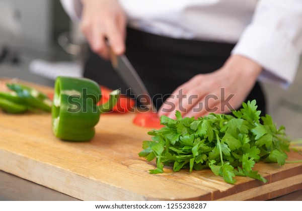 Сhef cook makes salad. closeup woman's hand cuts a tomato with a knife. parsley and green pepper on the cutting board in front