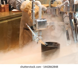 Cook making desert with dry ice heavy steam in professional kitchen