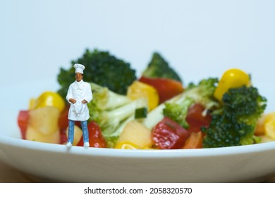 a cook as a miniature figure stands on a plate rim, in the background a white plate with a colorful vegetarian salad, broccoli, bell pepper, corn, apple and pine nuts