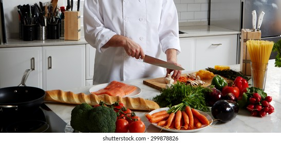 Cook is near the table, cut vegetables to fry them in a skillet and add to the Spaghetti and salmon bake in the oven