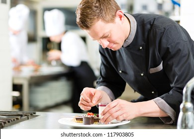 Cook, the pastry chef, in hotel or restaurant kitchen cooking, he is finishing a sweet dessert