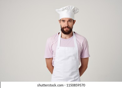 cook in a pink T-shirt in a white apron