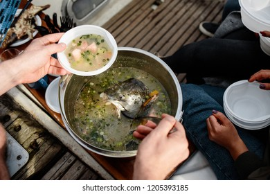 cook pouring fish soup