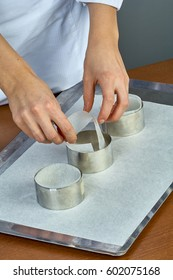 The cook pours the dough into forms for making cupcakes